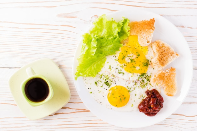 Scrambled eggs, fried bread, ketchup and lettuce leaves on a plate, coffee in a cup on the table