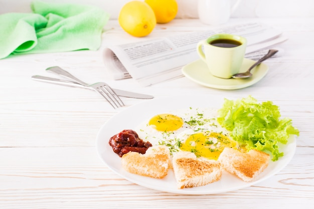 Scrambled eggs, fried bread, ketchup and lettuce leaves on a plate, cup of coffee and newspaper on the table.