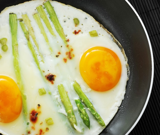 Scrambled eggs in a frying pan with asparagus