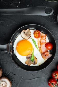 Яичница на сковороде со свиным салом, хлебом и зелеными перьями на чугунной сковороде, на черном