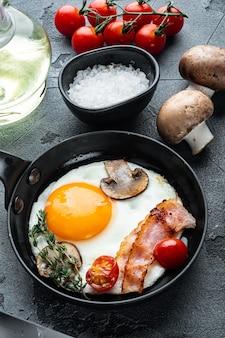 회색 배경에 주철 프라이팬에 돼지 고기 라드, 빵과 녹색 깃털이 달린 프라이팬에 스크램블 에그