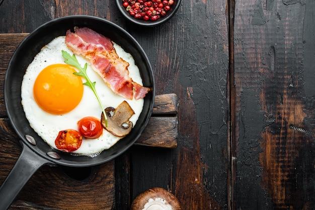 Яичница на сковороде со свиным салом, хлебом и зелеными перьями на чугунной сковороде, на фоне старого темного деревянного стола, плоская планировка, вид сверху,