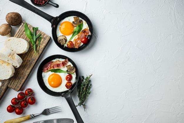 Яичница на сковороде со свиным салом, хлебом и зелеными перьями в чугунной сковороде, на белом фоне, плоский вид сверху, с пространством для текста copyspace