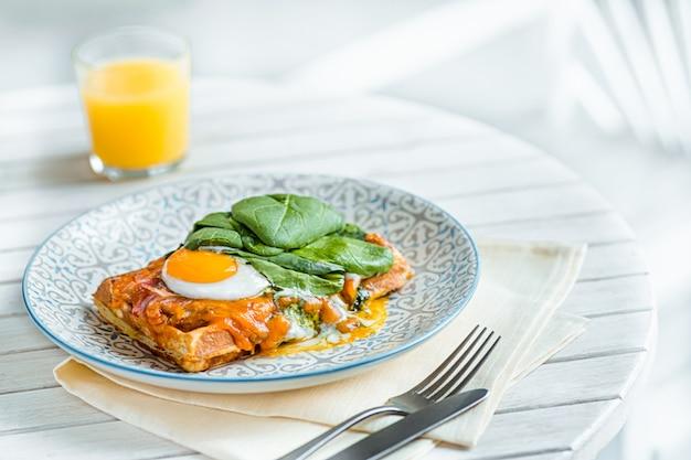 Uova strapazzate su carne con patate fritte e pane tostato al piatto sul tavolo di legno