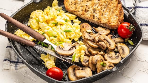 スクランブルエッグ、トーストとキノコ。健康的な朝食またはブランチ。自家製の食事。