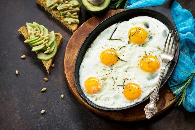 Яичница на сковороде кастирон и бутерброд со свежими ломтиками авокадо и кедровыми орехами концепция здорового питания вид сверху