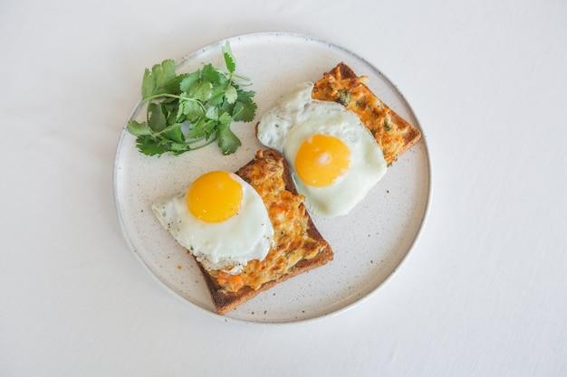 Яичница на тосте с плавленым сыром и кинзой на белой тарелке
