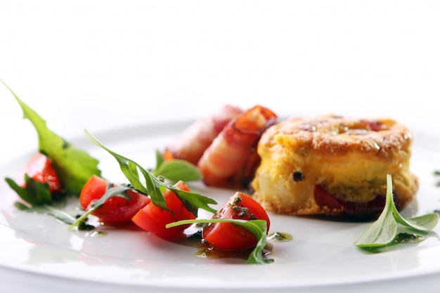 Scrambled eggs served with bacon and green