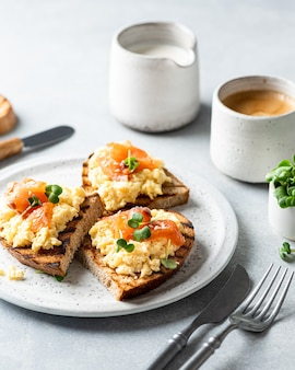 Scrambled eggs toast with salmon and coffee , selective focus