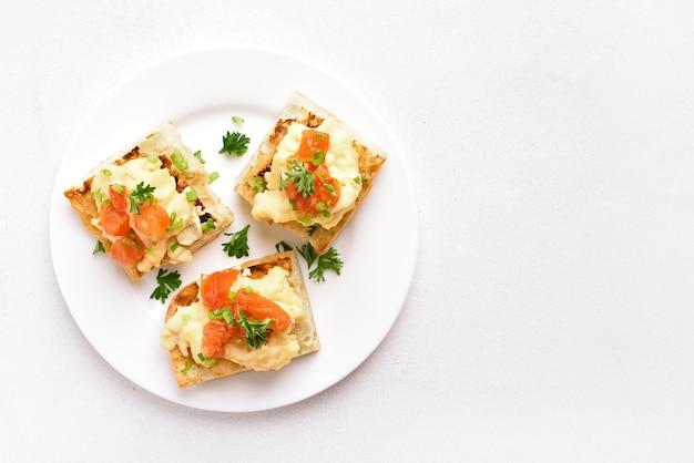 Scrambled eggs, tomato, green onion on bread
