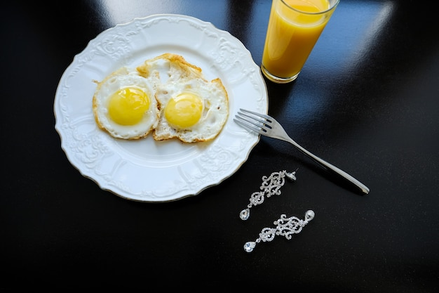 Scrambled eggs on a white plate, orange juice. next are the bride's earrings.