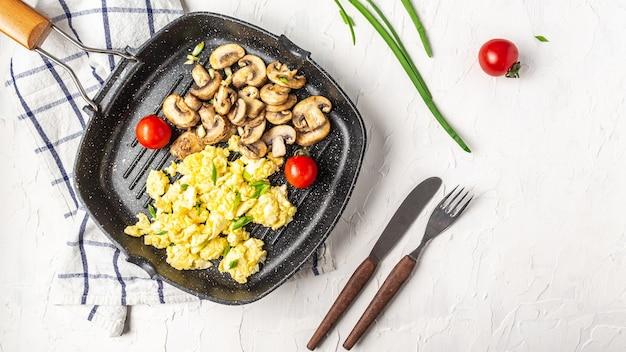 건강 한 아침 식사 또는 브런치, 평면도, 복사 공간에 대 한 프라이팬에 샴 피 뇽 버섯과 계란 스크램블. 수제 식사 레시피 스크램블 에그.
