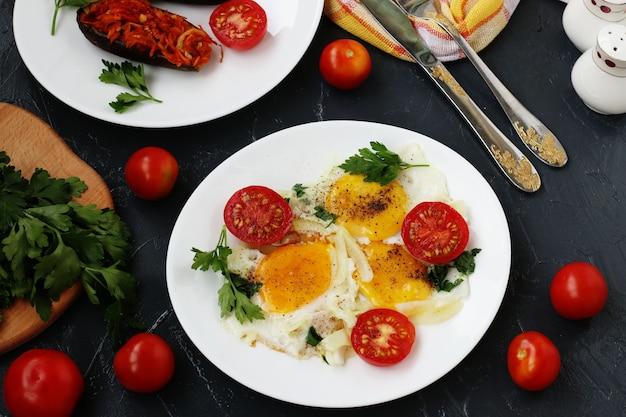 Яичница с помидорами черри расположена на белой тарелке на темном фоне, на фото там запеченные баклажаны, петрушка, столовые приборы, вид сверху