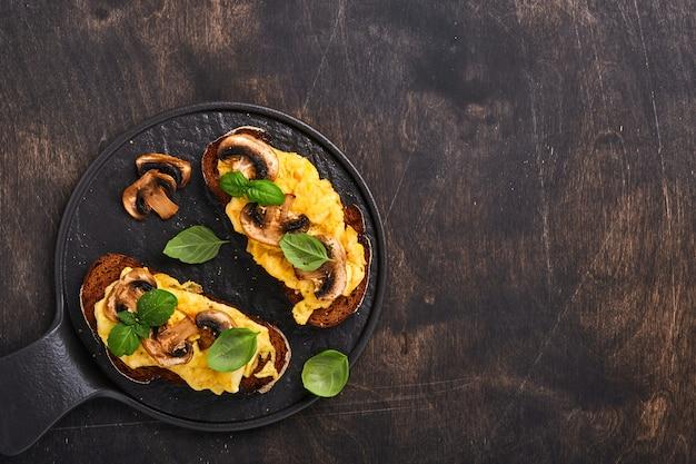 검은 테이블 배경에 빵에 튀긴 버섯과 바질을 곁들인 스크램블 에그. 집에서 만든 아침 식사 또는 브런치 식사 - 스크램블 에그와 버섯 샌드위치. 복사 공간이 있는 상위 뷰