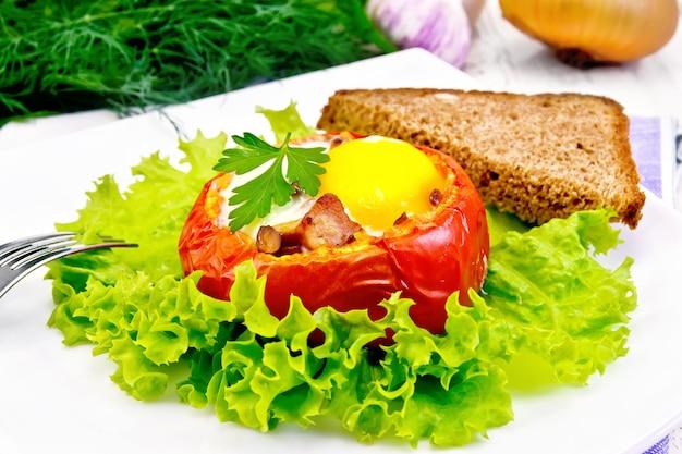 木の板の背景に、プレート、パン、フォークの緑のレタスにトマトにハムとキノコを入れたスクランブルエッグ