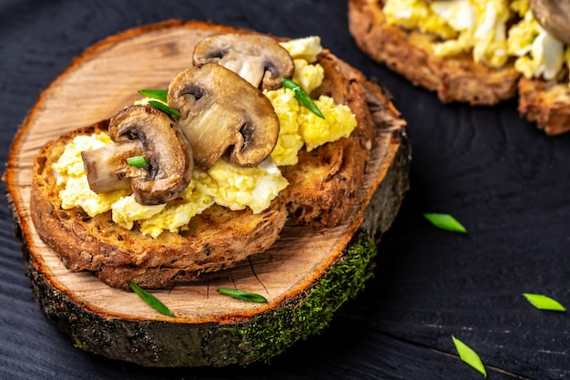 自家製の小麦ライ麦クリスピーパンにハーブとスクランブルエッグ。健康的な朝食またはブランチ。食品レシピ表。閉じる。