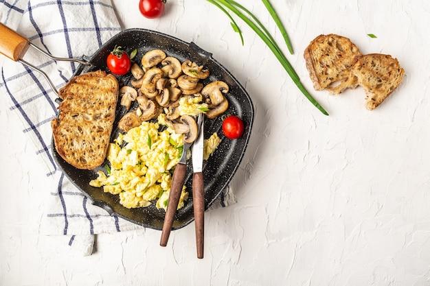 白いテーブルの上の鍋にキノコとスクランブルエッグ。健康的な朝食またはブランチ。自家製の食事、上面図、フラットレイ。