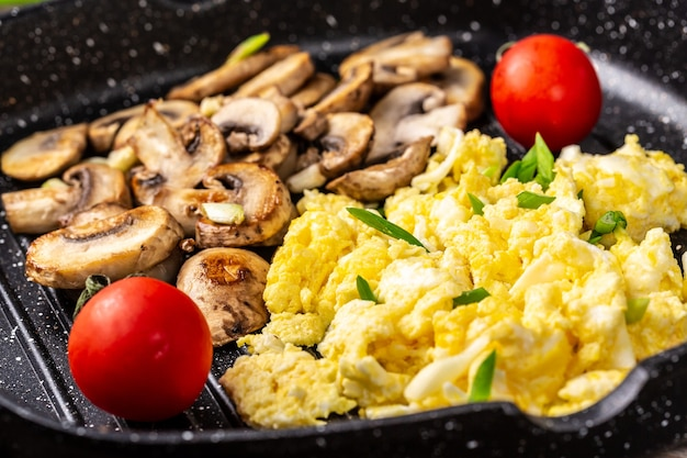 Scrambled eggs with mushrooms, tomatoes in pan