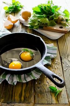 Яичница с крапивой в сковороде на деревянный стол