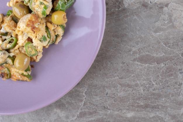 Яичница с оливками на фиолетовой тарелке.