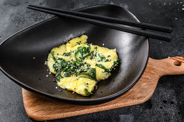 Scrambled eggs with spinach and parmesan cheese with sesame. black background. top view.