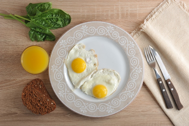 Scrambled eggs with spinach on the plate with a healthy breakfast with orange juice
