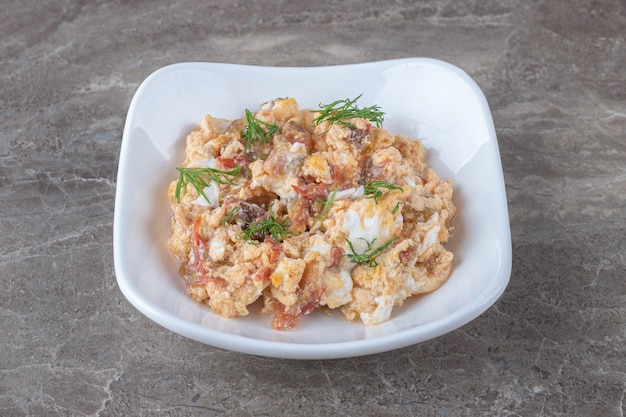Scrambled eggs with various vegetables in white bowl.