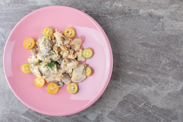 Scrambled eggs with vegetables on pink plate.