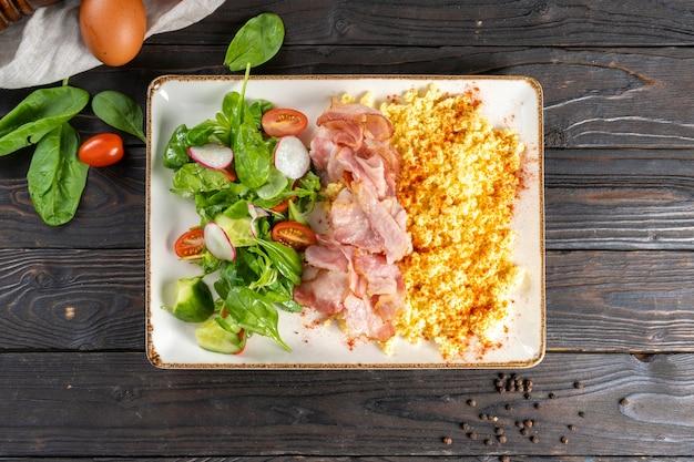 ベーコンと野菜のサラダを添えたスクランブルエッグ。
