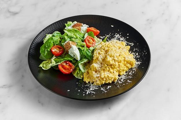 Омлет-болтунья с салатом из шпината, сыром рикотта и помидорами черри, подается в черной тарелке на мраморной поверхности