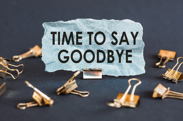 A scrap of blue paper with clips on a gray surface with the text - time to say goodbye.