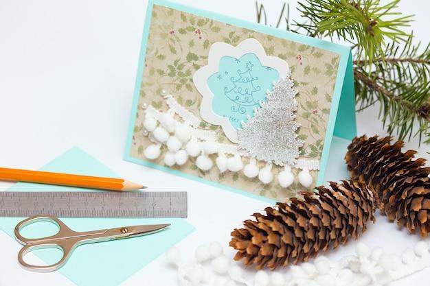 スクラップブックの背景のクリスマスカードと装飾が施されたツール