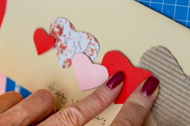 スクラップブックの背景。バレンタインデーにポストカードを作る女の子