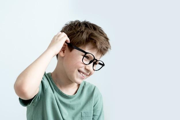 스크래치, 녹색 티셔츠와 안경에 놀란 소년 잠겨있는 그의 머리를 긁적