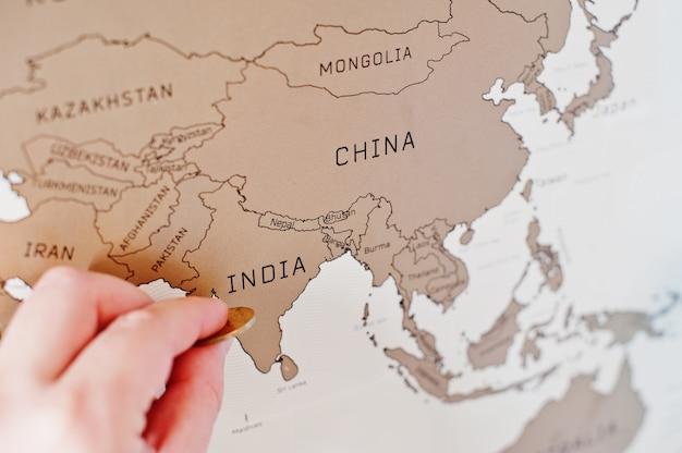 Скретч путешествия карта мира, рука человека сотрут индию с монеты.