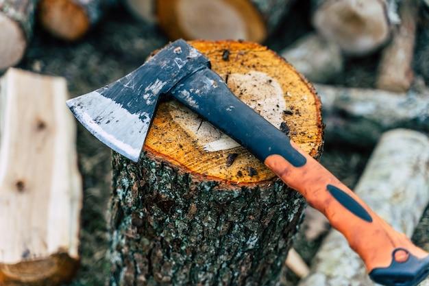 アルダーログにオレンジ色のハンドルが付いた傷のある斧-ハードワークコンセプト