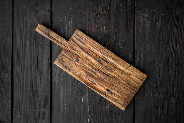Набор поцарапанной разделочной доски, плоская планировка, вид сверху, с копией пространства для текста или еды, на черном фоне деревянного стола
