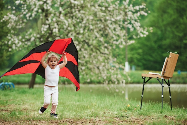 Scream of happiness. positive female child running with red and black colored kite in hands outdoors