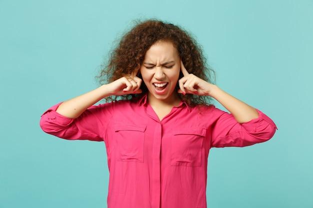スタジオで青いターコイズブルーの背景に分離された指で耳を覆って目を閉じたままカジュアルな服を着て叫んでアフリカの女の子。人々の誠実な感情、ライフスタイルのコンセプト。コピースペースをモックアップします。
