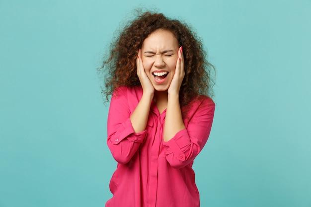Ragazza africana urlante in abiti casual rosa tenendo gli occhi chiusi, coprendo le orecchie con le mani isolate su sfondo blu turchese muro. persone sincere emozioni, concetto di stile di vita. mock up copia spazio.