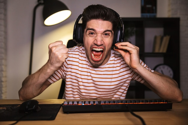 Screaming angry gamer playing video games on computer