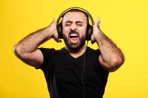 수염을 가진 아랍 남자 비명은 노란색 헤드폰으로 음악을 수신합니다. 국제 dj의 날