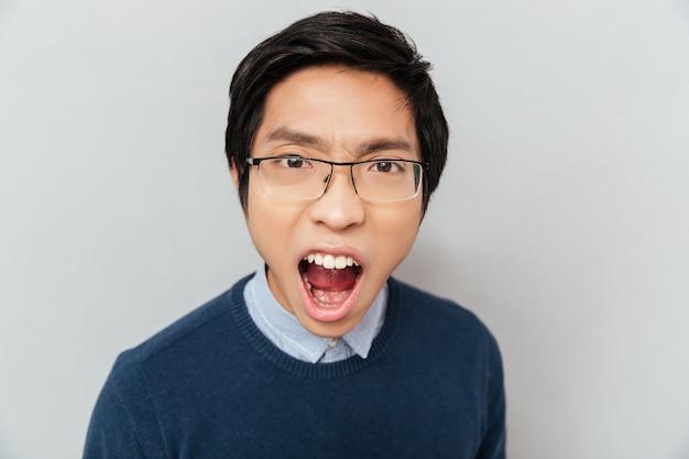 悲鳴を上げるアジアの学生。カメラを見て