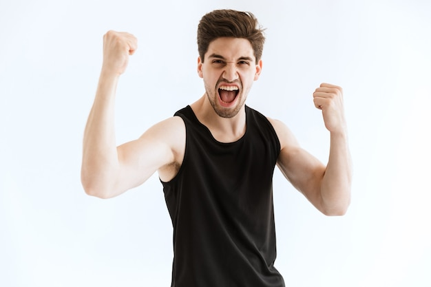 Screaming attractive strong young sports man running and make winner gesture.