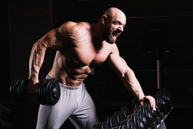 Screaming bald man lifting dumbbell
