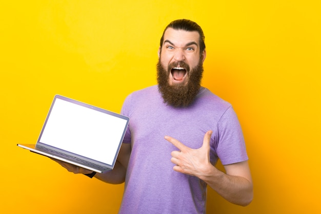 Screaming bearded man is pointing at the laptop.