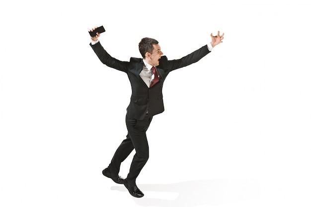 白いスタジオで携帯電話を実行している実業家を叫んでください。
