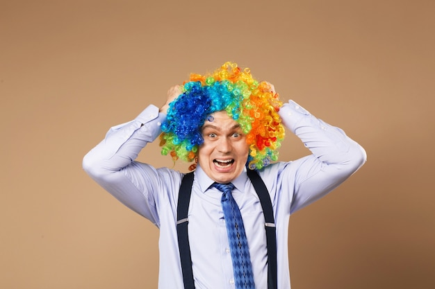 Screaming businessman with large colorful wig. close-up portrait of business man in clown wig. business concept