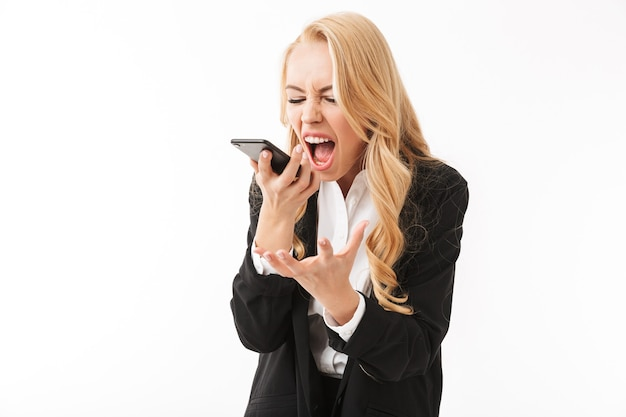 電話で話している白い壁に分離されたポーズ不機嫌なビジネス女性の叫び。