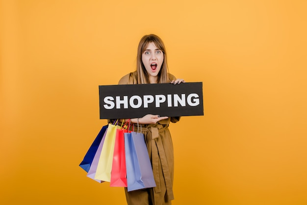 Screaming emotional woman in trench coat with shopping  sign and colorful shopping bags isolated over yellow